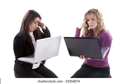 Two women with laptops looking frustrated with what they are doing.