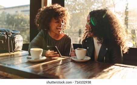Two women laughing looking at a mobile phone inside a coffee shop. Woman sitting with coffee cups on the table having fun.