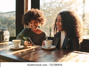 Two women laughing looking at a mobile phone inside a coffee shop. Friends sitting with coffee cups on the table having fun.