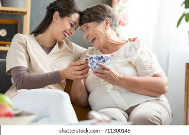 Two women laughing together at a funny joke during afternoon tea break in retirement home
