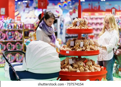 two women like gay couple or friends with white baby carriage is looking some toy bear for kid in the big colorful supermarket