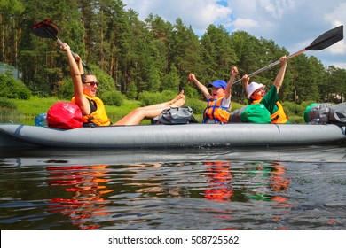 Two women and little boy have fun on inflatable boat on river at sunny summer day