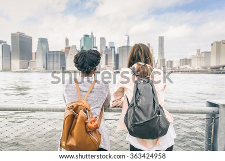 Two women looking at New York skyline - Multiethnic girls leaning on a railing and watching at cityscape