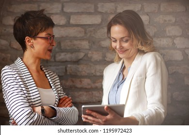 Two women looking on ipad and talk about business indoor