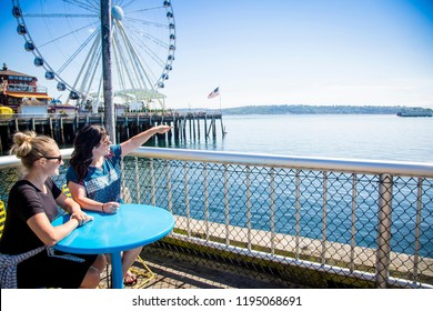 Two women looking out at the Seattle harbor on a sunny day. Sitting at a table on the waterfront near the Ferris Wheel and pier