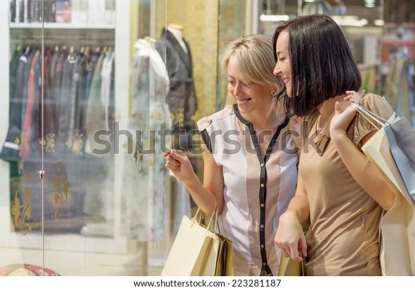 Two women looking through shop window