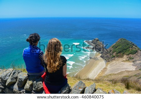 Two women looking at the view from Cape Reinga, north edge of New Zealand.