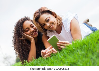 Two women, lying face down on the ceped using a smartphone