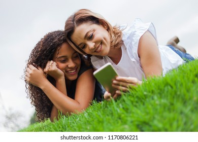 Two women, lying face down on the ceped using a phone