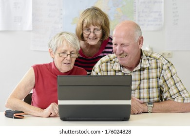 Two women and a man looking at a laptop screen.