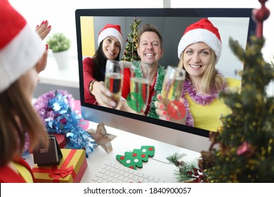 Two women and man in santa claus hats with glasses of champagne in hands congratulate friend happy new year and merry christmas through computer screen. Remote new year greetings during the covid 19