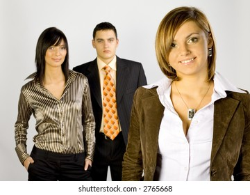 Two women and a man are standing, looking at the camera and smiling. There's woman-leader at the front of group. Horizontal.