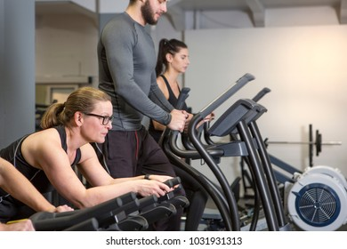 Two women and a man training in cardio machines at a gym. They look focused.