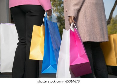 Two women with many shopping bags