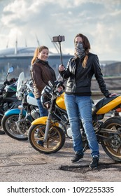 Two women motorcyclists make photo with selfie stick and front camera of cellular