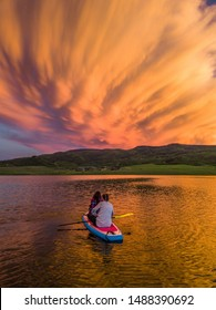 Two Women on a Stand Up Paddle Board at Sunset Looking Over a Mountain Range at Stagecoach State Park in Colorado, USA
