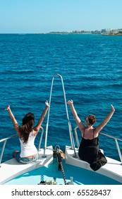 Two women on yacht in blue sea.