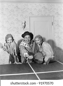 Two women and one man in a costume playing table tennis