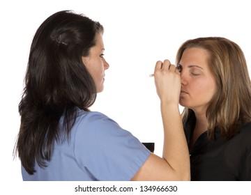 Two women one a very technical and professional beauty technician in scrubs work cloths applying make up on a blond woman's face. In studio on white background.