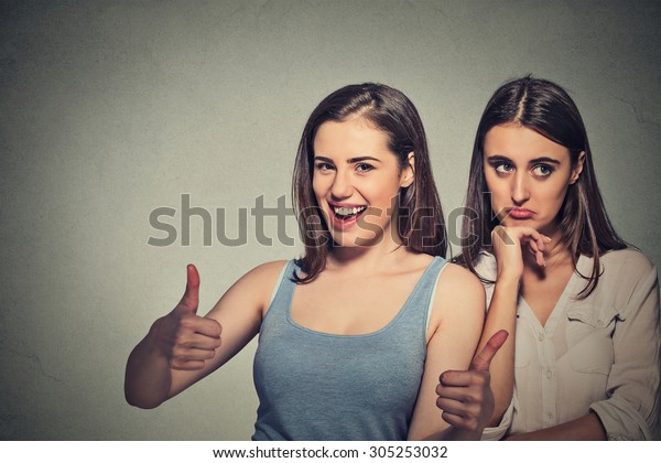 Two women optimistic lady having solution and bored, annoyed clueless sad woman on gray wall background. Human emotion face expression feeling, life approach. Bipolar disorder concept