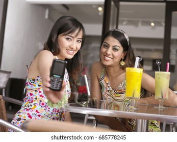 Two women at outdoor cafe, taking pictures
