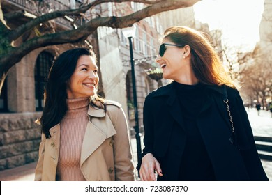 Two women outdoors having fun. Female friends on walking down the street and smiling outdoors.