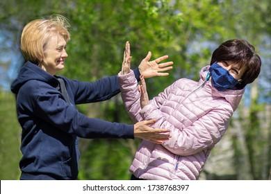 Zwei Frauen im Freien, eine in Schutzmaske im Gesicht, wollen nicht eine andere ohne Maske umarmen, um zu umgehen. Bewahren Sie soziale Distanz, Virus, Gesundheitscoronavirus-Konzept. Covid-19. Stoppen