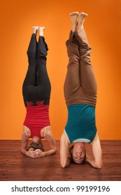 Two women perform Sirsasana headstand positions over orange background