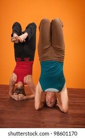 Two women perform Vrisikasana yoga posture over orange background
