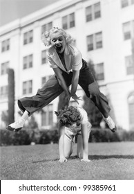 Two women playing leap frog together