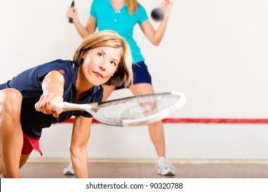 Two women playing squash as racket sport in gym