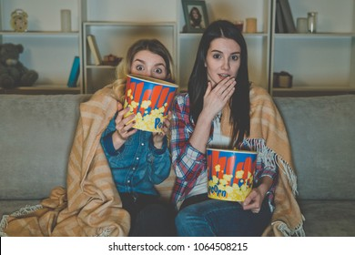 The two women with a popcorn watch a horror movie on the sofa