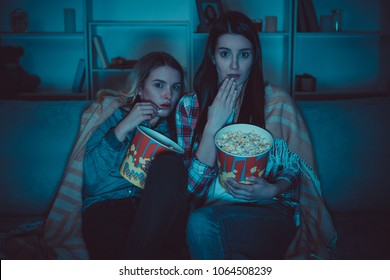 The two women with a popcorn watch a horror film on the sofa