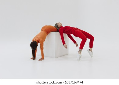 two women posing on white cube