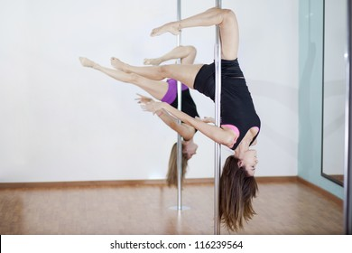 Two women practicing a pose in a pole fitness class