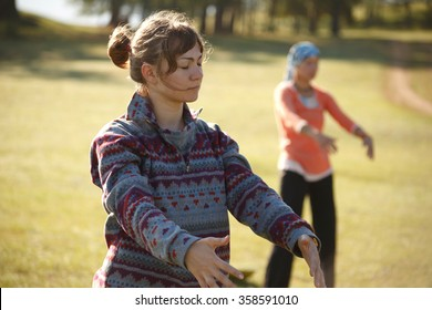 Two women are practicing Qi Gong