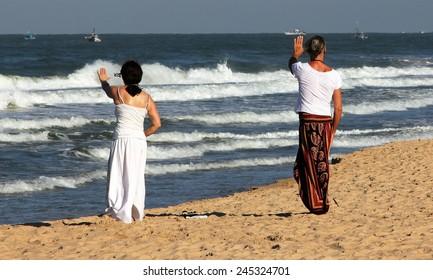 Two women practicing Qigong on the beach of Goa, India