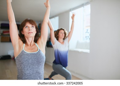 Two women practicing yoga forms and positions in gym. Fitness females doing warrior pose at yoga class. Virabhadrasana posture in training session.