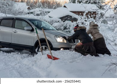 two women pushing a car stuck in the snow