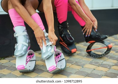 two women put on kangoo jumping boots before workout. Closeup shot with hands