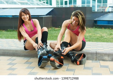 two women put on kangoo jumping boots and smiles. beautiful girls wearing shoes before outdoor fitness workout.