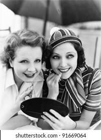 Two women putting on makeup