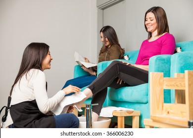 Two women relaxing and having a good time at a nail salon while getting a pedicure