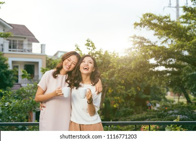 Two Women Relaxing On Rooftop Garden Drinking Coffee