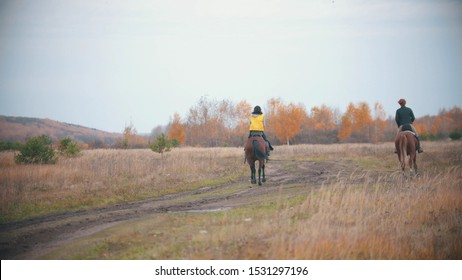 Two women are riding ginger horses on the autumn field