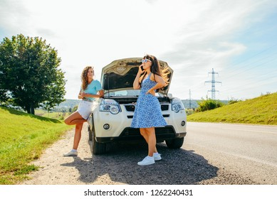 two women at roadside calling car service. broken car. car travel