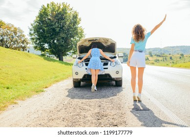 two women at roadside need help with broken car. car travel