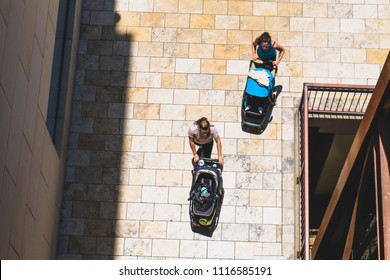 Two women rolling baby bassinet strollers on the street on a sunny day in summer. Top view of women with strollers. Walking babies