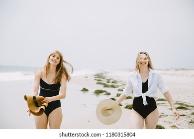 Two women running at the beach and laughing