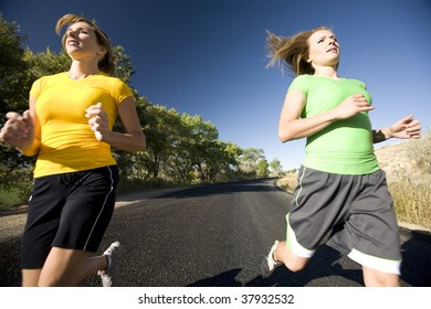 Two women running fast and racing down the road.